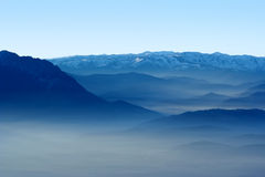 Mountains and valley in the fog. View of a valley and blue mountains in the fog Stock Photo