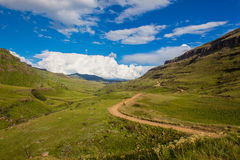 Mountains Valley Road Pass Summer. Summer at Sani Pass overlooking the  dirt road high in mountains. Picture photo image looking down the valley between the Royalty Free Stock Images