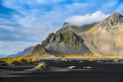 Mountains and volcanic lava sand in Stokksness, Iceland Stock Photo