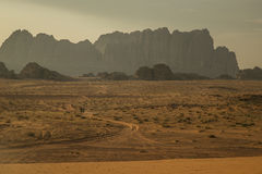 Mountains in Wadi Rum desert with desert road and small car Royalty Free Stock Image