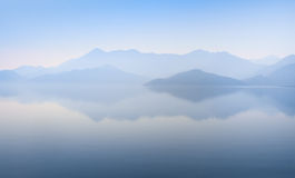 Mountains and waterscape. Mountain peaks covered with blue mist and still waterscape on the background in Montenegro Stock Photo