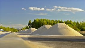 Mountains of white sand lie on side of road. Construction of high-speed ring road around Krasnoe Selo, Saint Petersburg. Civil and industrial construction stock video