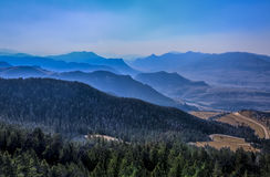 Mountains and winding road. Dead Indian Summit Overlook on the Chief Joseph Highway in the Shoshone Natl Forest, Wyoming, smoky after nearby forest fires Stock Image