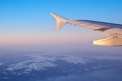 Mountains and wing of an airplane Stock Images