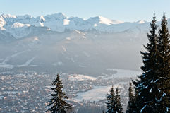 In the mountains, winter landscape. The city visible in the valley. Photography in the mountains in winter. Beautiful blue sky and mountains in the snow. The Stock Photo