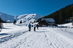 In the mountains, winter landscape. Photography in the mountains in winter. Beautiful blue sky and mountains in the snow. The road, which roam the people. House Royalty Free Stock Photography