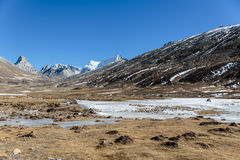 Mountains witn snow and below with tourists on the ground with brown grass, snow and frozen pond in winter at Zero Point. Royalty Free Stock Photos