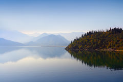 Mountains, woods and waterscape. Mountain peaks covered with blue mist, still waterscape and autumn woods on the background in Montenegro Royalty Free Stock Photos