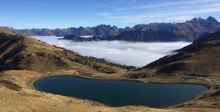 Mountainsee mit Bergen und Nebel im Hintergrund stockbild