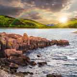 Mountainsee mit felsigem Ufer bei Sonnenuntergang Lizenzfreies Stockfoto