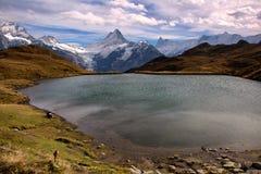 Mountainsee mit Wolken und weißen Gebirgsspitzen lizenzfreie stockfotos