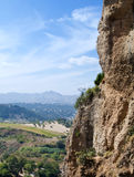 Mountainside. In the Spanish town of Ronda in the province of Malaga. skies are cloudy, and a landscape of shrubs in the background Royalty Free Stock Photography