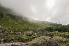 Mountainside with bushes covered with clouds. Mountain side in covered by clouds. Grass, rocks, snow Stock Images