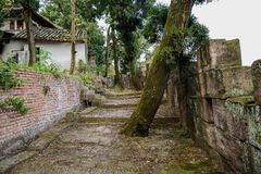 Mountainside Chinese aged buildings along ruined stone path and Royalty Free Stock Photo
