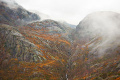 Mountainside with descending mist. Autumn mountainside with tiny waterfall and descending mist Royalty Free Stock Photo