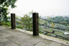 Mountainside footpath with chained stone balusters in cloudy fog Royalty Free Stock Photo