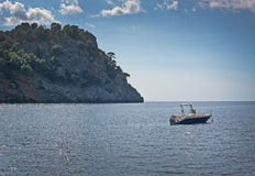 Mountainside sea moored boat. Glitter and horizon in Mallorca, Spain Stock Photography