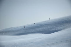 Mountainside ski slope. People skiing on a snowy mountainside royalty free stock images