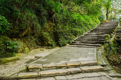 Mountainside stone paved path and steps in winter afternoon Royalty Free Stock Photos