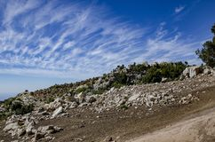 The mountainside is strewn with stones and in the background incredibly beautiful clouds. In the sky Stock Photography