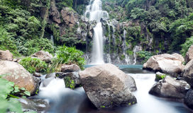 Mountainside waterfall. Slow shutter for moving water at Trois Bassin waterfall on Reunion Island stock photos