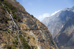 Mountainside Waterfall. A waterfall flows down the steeps canyon walls of Tiger Leaping Gorge in Yunnan Province, China Royalty Free Stock Photo