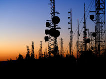 Mountaintop Communication Towers at Sunset. Mountaintop Communications towers with red beacons silhouette the night sky at sunset Stock Photos