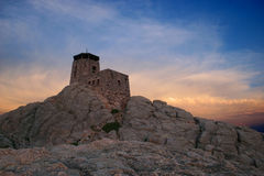 Mountaintop fortress. Castle fortress on mountaintop with dramatic sunset sky Royalty Free Stock Images