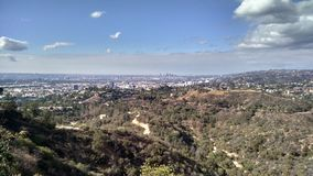 Mountaintop View of Los Angeles California with forest and light cloud cover royalty free stock photography