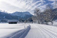 Mountan Landschaft des Winters mit gepflegter Skibahn und blauem Himmel am sonnigen Tag, schneebedeckte Bäume entlang der Straße lizenzfreie stockfotos