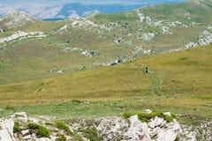 Mountanious toneel leeg landschap met lopende toeristen royalty-vrije stock afbeelding