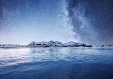 Mountans and reflection on the water surface at the night time. Sea bay and mountains at the night time. Milky way above mountains. Norway. Beautiful natural stock image