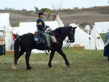 Mounted Cavalry-Trail of History. McHenry County's Trail of History reenactment of mounted cavalry officer on black horse walking in front of white canvas tents Royalty Free Stock Image
