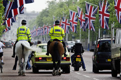 Mounted police on the Mall, London. LONDON, UK - APRIL 28, 2011: Mounted police on the Mall decorated with Union Jack flags in preparation of the Royal Wedding Stock Photos
