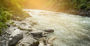 Mountian river with cristal water on sunlight nature background. River with cristal water on sunlight nature background stock image