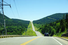 Mountian road in northern Canada. Mountain road in black spruce boreal forest of Canada with electric pilones close by, parc des laurentides, quebec Royalty Free Stock Photography