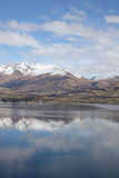 Mountians reflected in clear lake. New Zealand mountains reflected in the clear waters of Lake Wakatipu Stock Image