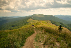 Mountin path in Bieszczady. Poland,summer.Tourist path in Bieszczady mountin.Far one can see the group of tourists going along the trail into the bottom Royalty Free Stock Photos