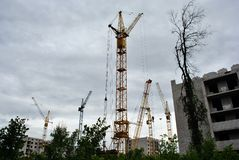Mounting cranes at construction of apartment building, trees in the foreground, horizontal composition, cloudy sky. Background royalty free stock images
