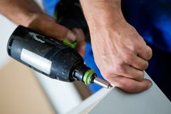 Mounting furniture with screwdriver Royalty Free Stock Photography