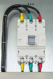 On a mounting plate or Board fixed power circuit breaker. Connected electrical cables in insulation top and bottom. The handle of the circuit breaker in the stock image