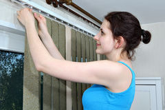 Mounting shutters, Girl hook fabric blinds slats, Install blinds. Install blinds. Girl hanging blinds, vertical blind fabric slats hook onto rail. Free hanging Stock Images