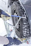 Mounting snow chains. Car driver mounts snow chains on the tyre of his car royalty free stock photo