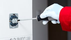Mounting Socket. Electrician installing new current socket with screwdriver Stock Image