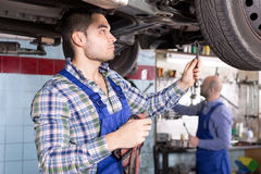 Mounting specialists in coveralls working. Adult male mounting specialists working at auto repair shop Royalty Free Stock Photo