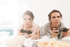 The mournful girls are playing on the console. They lie on a bed in a bright room. Stock Photos