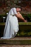 Mournfull-Frau im weißen Kleid, das auf einer Steinbank sitzt Lizenzfreie Stockfotos
