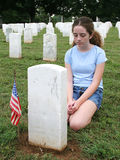 In Mourning. A girl in a military graveyard, mourning a fallen soldier Stock Photo