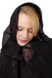 Mourning. Woman wrapped in black silk fabric looks down in thought or sadness. Woman dressed in black for mourning. Widow Stock Photo