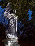 Mourning angel. Stone statue of mourning angel on a tombstone against the dusk sky Stock Photo